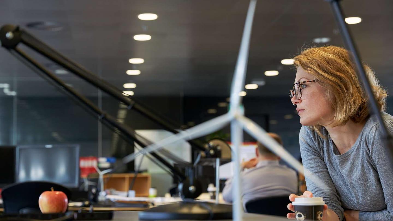 person arbetar vid datorn, vindkraftverk i förgrunden