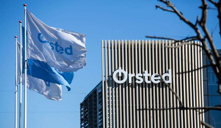 3 Ørsted flags fly outside of an Ørsted office on a sunny day.