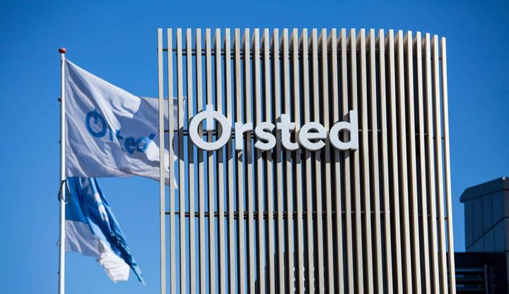 The Ørsted office is surrounded by blue sky and Ørsted flags flying.