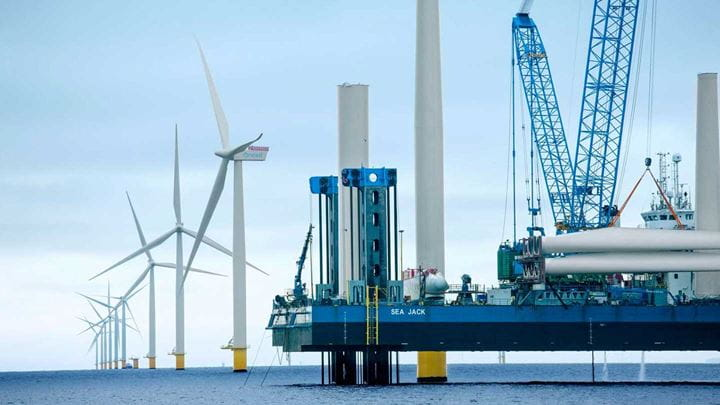 Blades turning on a group of offshore wind turbines in the sea.