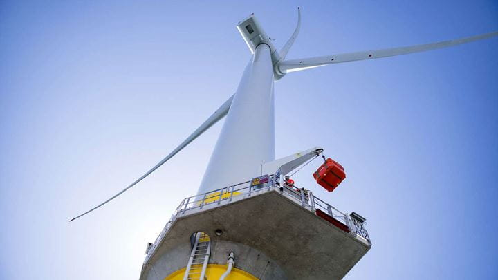 A low angled shot of a tall wind turbine surrounded by blue sky.