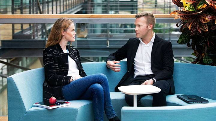 A man and a woman sit on a blue circular sofa for a meeting.