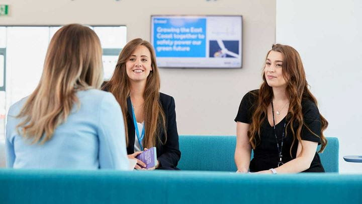 Three females in office attire sit on a blue sofa whilst talking.