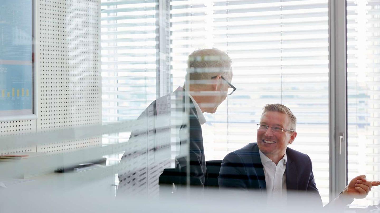 Two happy employees seen through window