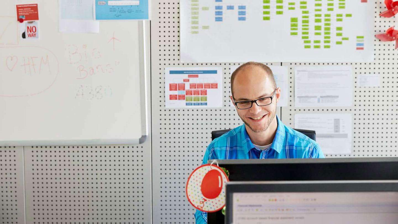 Smiling employee behind computer