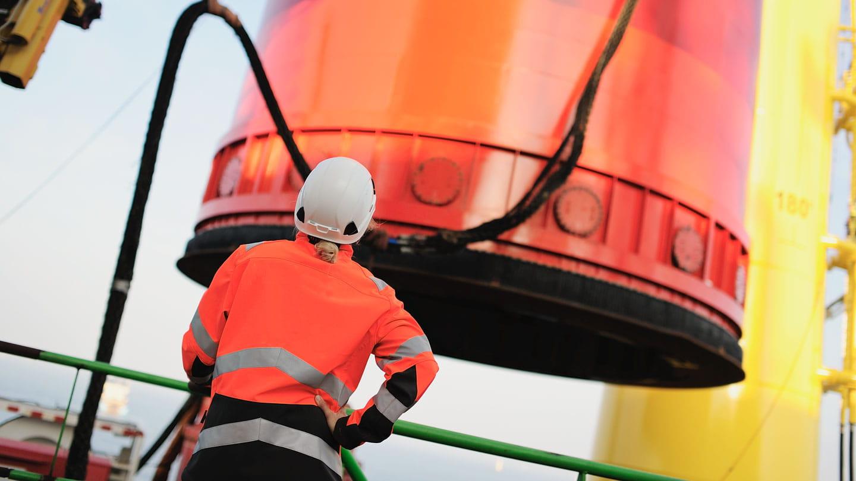 female employee wearing orange safety jacket works