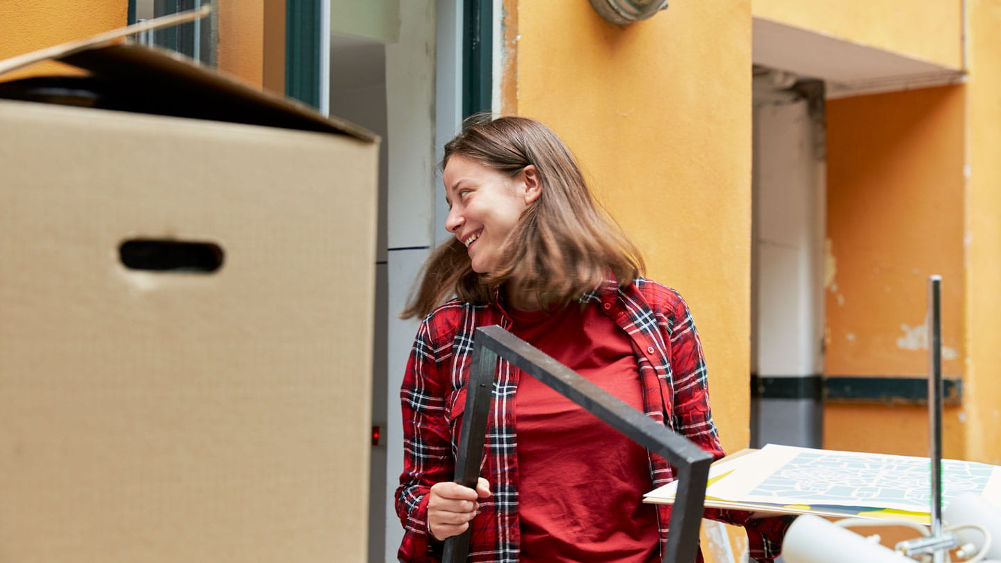 young woman moving picture frame and boxes