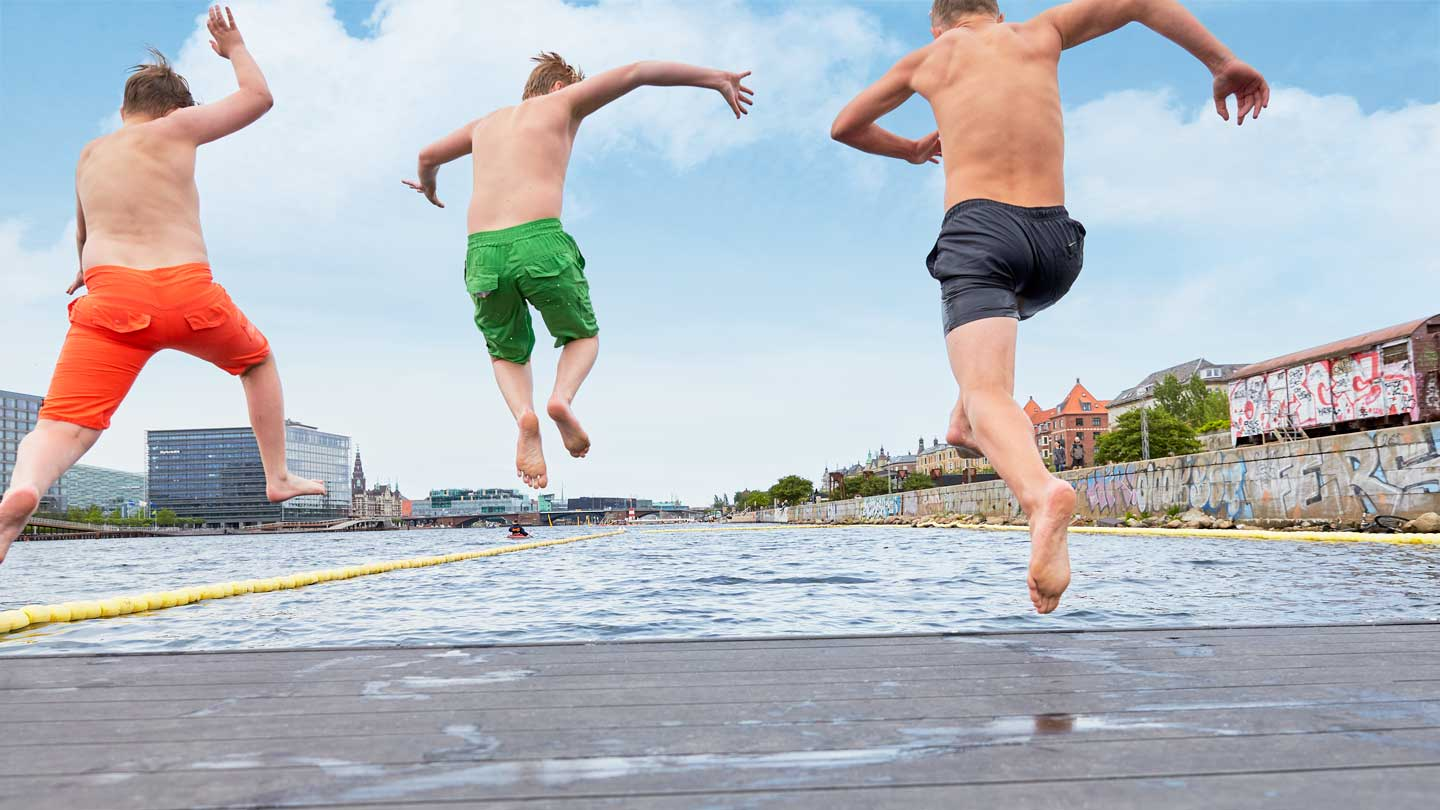 three young boys jumping of harbour in Copenhagen