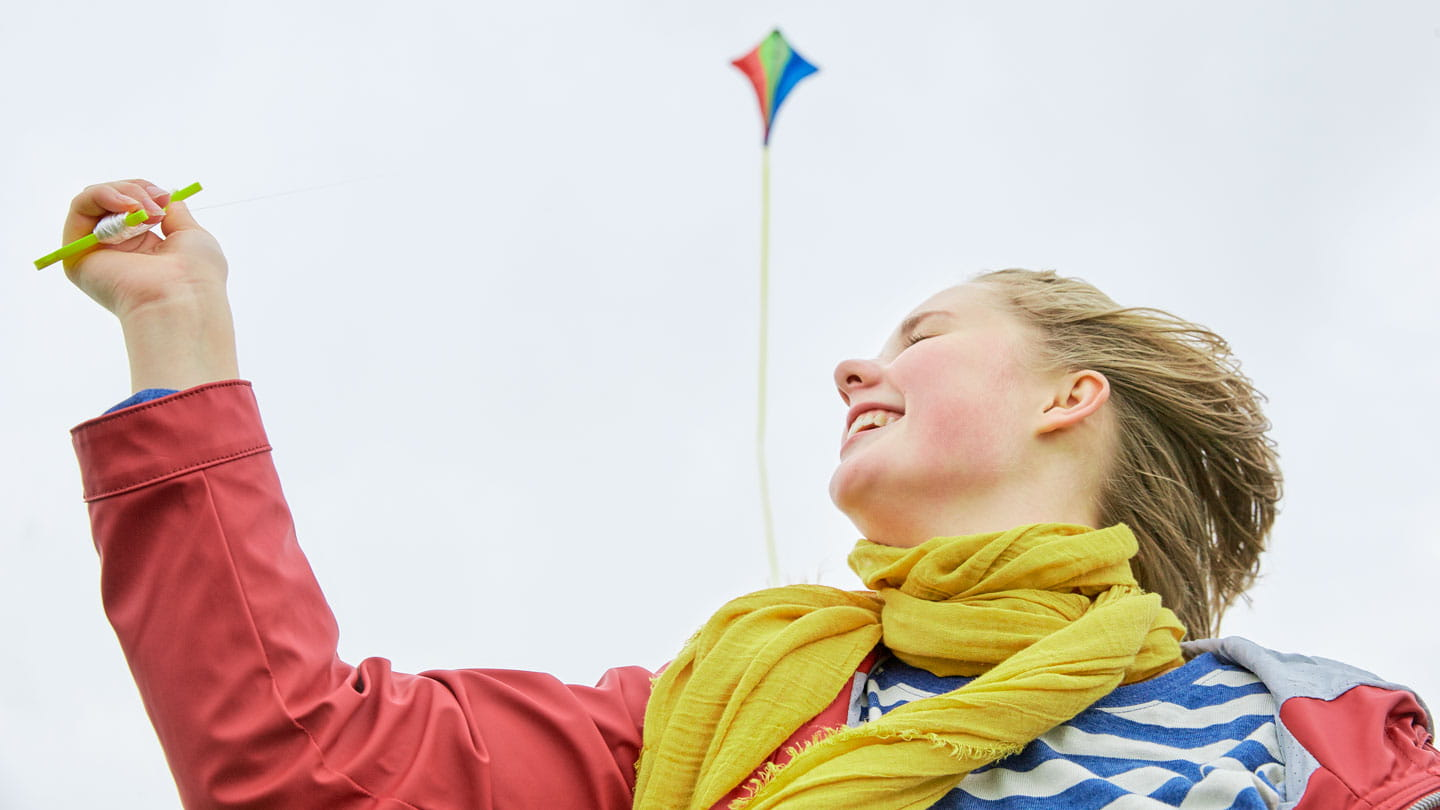 girl laughing outside while flying kite