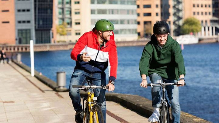 Two people wearing helmets ride bikes along the side of a river.