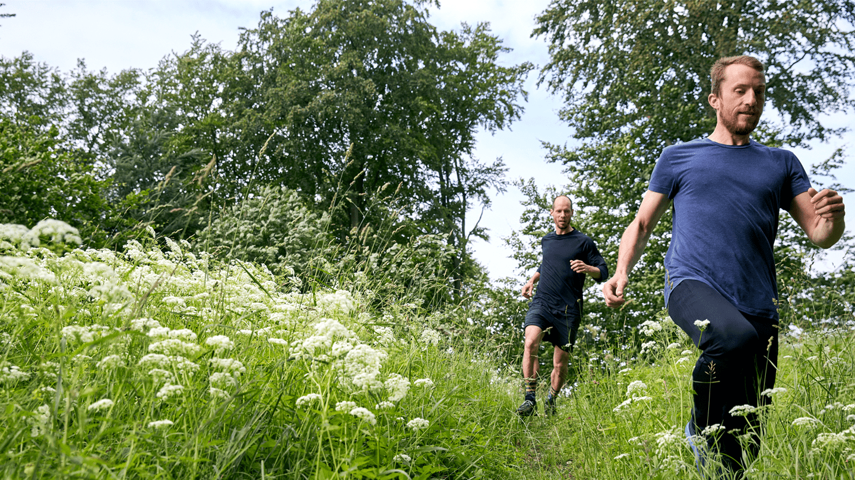 Guys running through grass