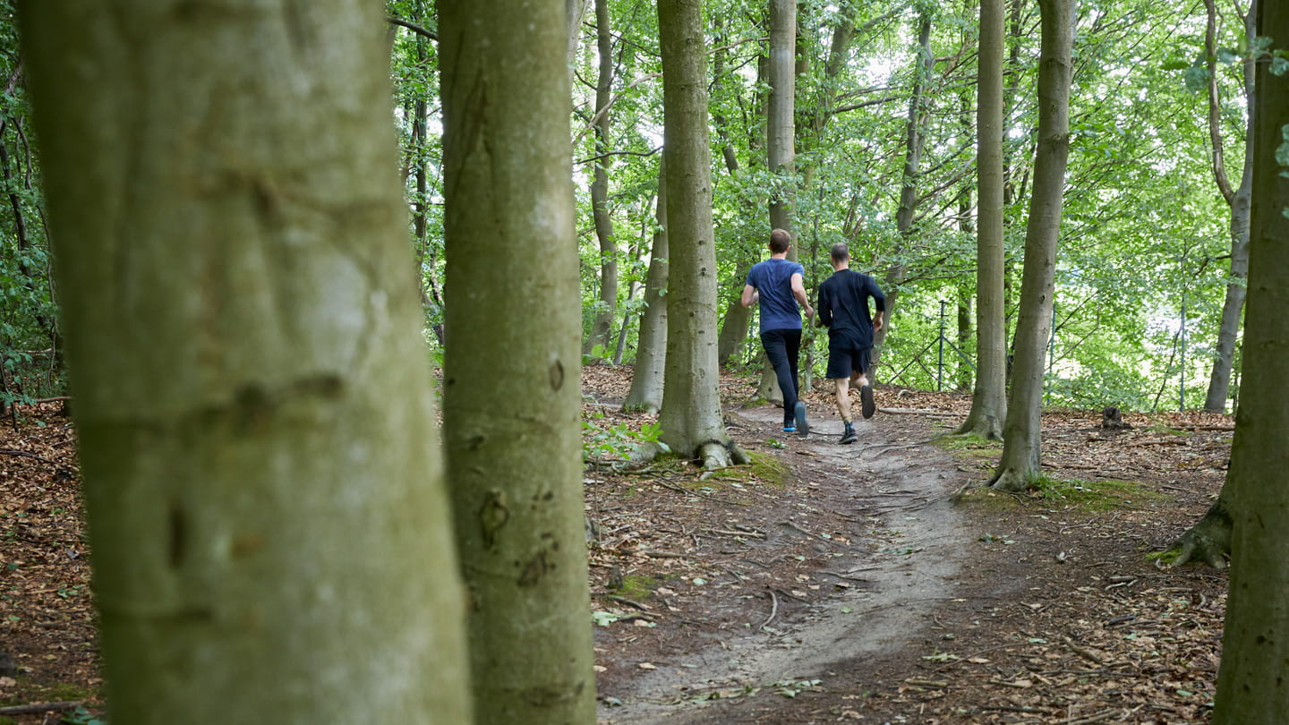 two men running in forest between trees