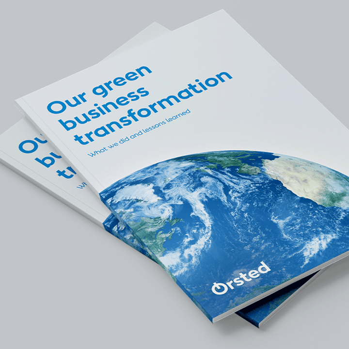 Two booklets entitled 'our green business transformation' sit on a surface.