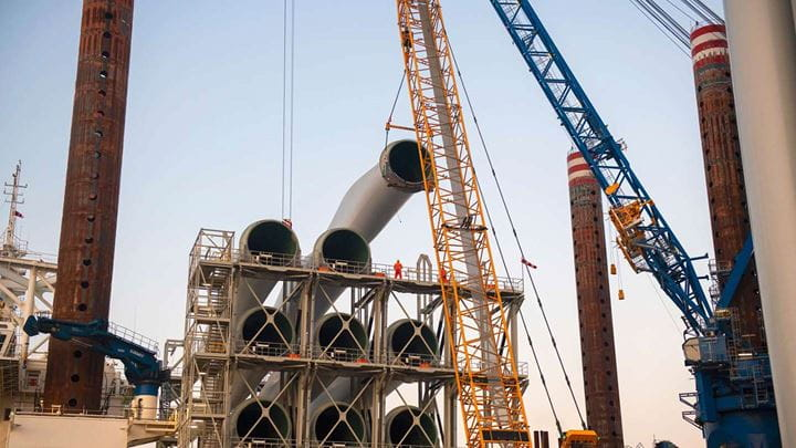 Cranes are used to secure heavy piping on a construction site.